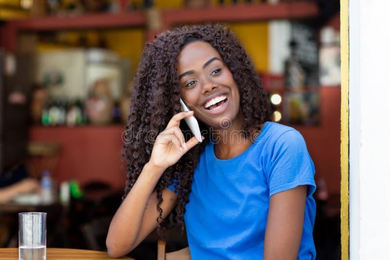 Afrikaanse Amerikaanse vrouw die bij bar bij mobiele telefoon lachen royalty-vrije stock afbeelding