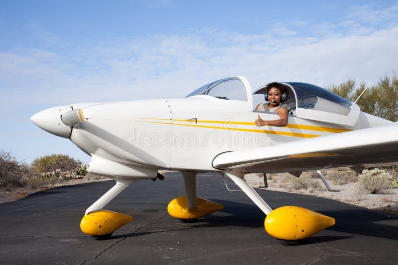 Afrikaanse Amerikaanse vrouw die een privé vliegtuig vliegt stock fotografie