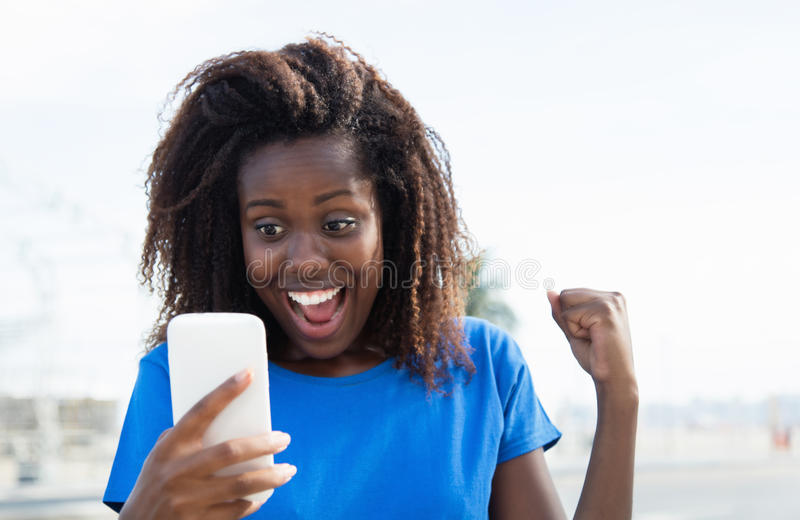 Afrikaanse Amerikaanse vrouw die goed nieuws ontvangen telefonisch stock foto