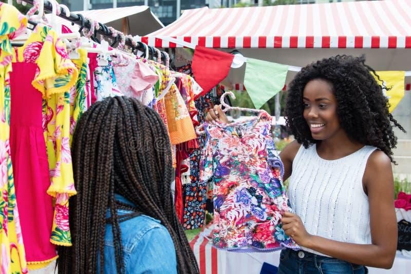 Afrikaanse Amerikaanse vrouw die kleurrijke kleren voorstellen bij markt stock fotografie