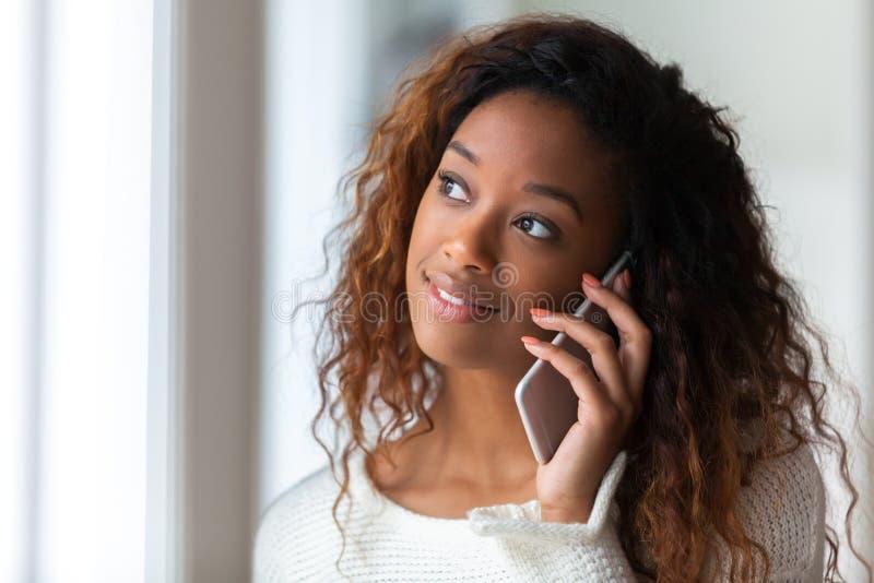 Afrikaanse Amerikaanse vrouw die op een mobiele telefoon spreken - Zwarte mensen royalty-vrije stock afbeeldingen