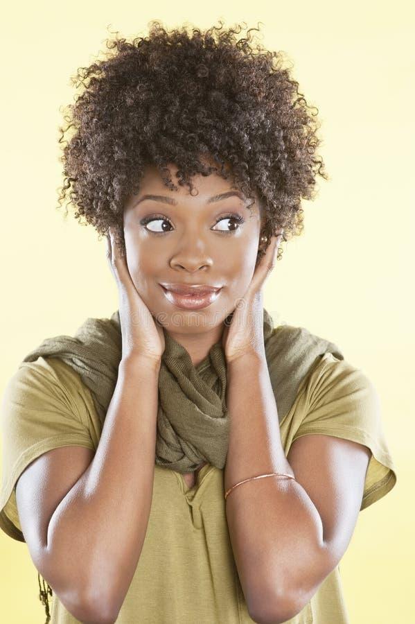 Afrikaanse Amerikaanse vrouw die zijdelings over gekleurde achtergrond kijken stock afbeelding