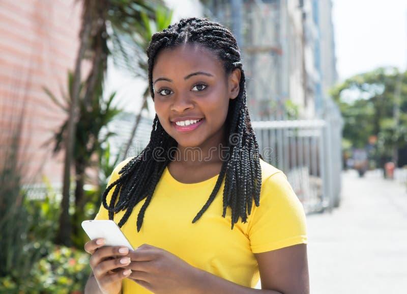Afrikaanse Amerikaanse vrouw in een geel overhemd het typen bericht met mobiele telefoon stock afbeelding