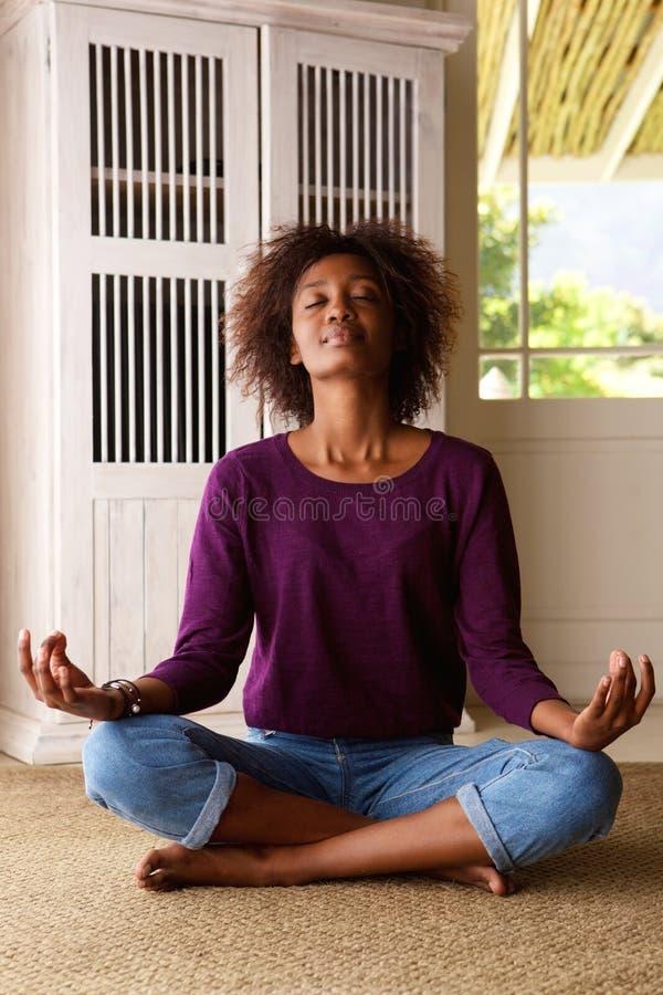 Afrikaanse Amerikaanse vrouw het praktizeren yoga thuis royalty-vrije stock foto
