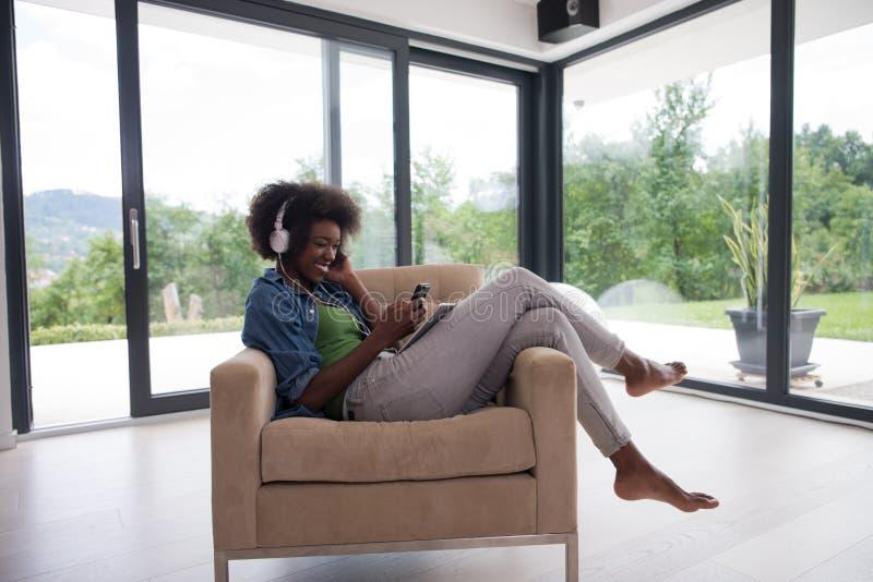 Afrikaanse Amerikaanse vrouw thuis als voorzitter met tablet en hoofdpho royalty-vrije stock foto