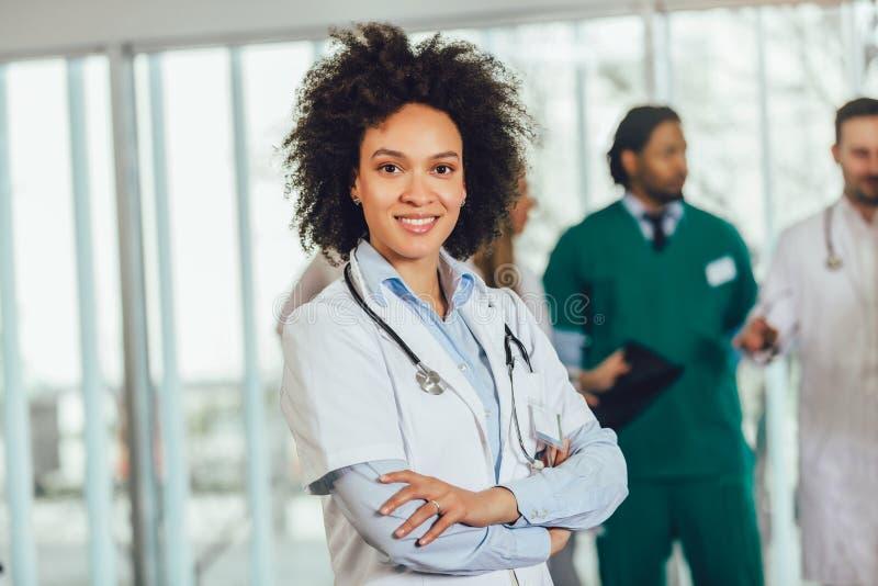 Afrikaanse Amerikaanse vrouwelijke arts die op het ziekenhuis camera het glimlachen bekijken royalty-vrije stock afbeelding