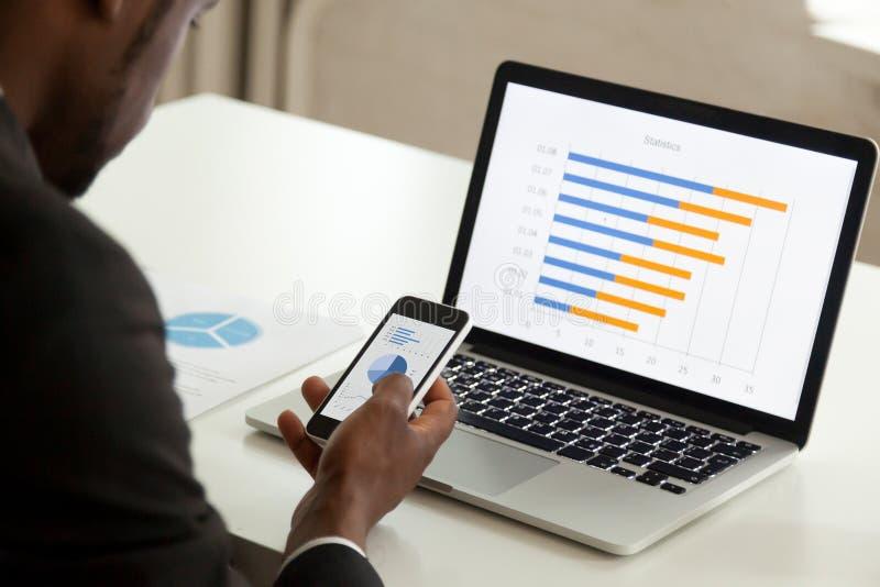 Afrikaanse Amerikaanse zakenman die apparaten voor zaken, over sh met behulp van royalty-vrije stock afbeelding