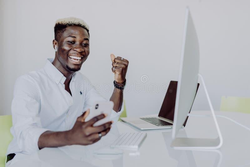 Afrikaanse Amerikaanse zakenman die geld witn handen maken omhoog op kantoor winnen stock foto's