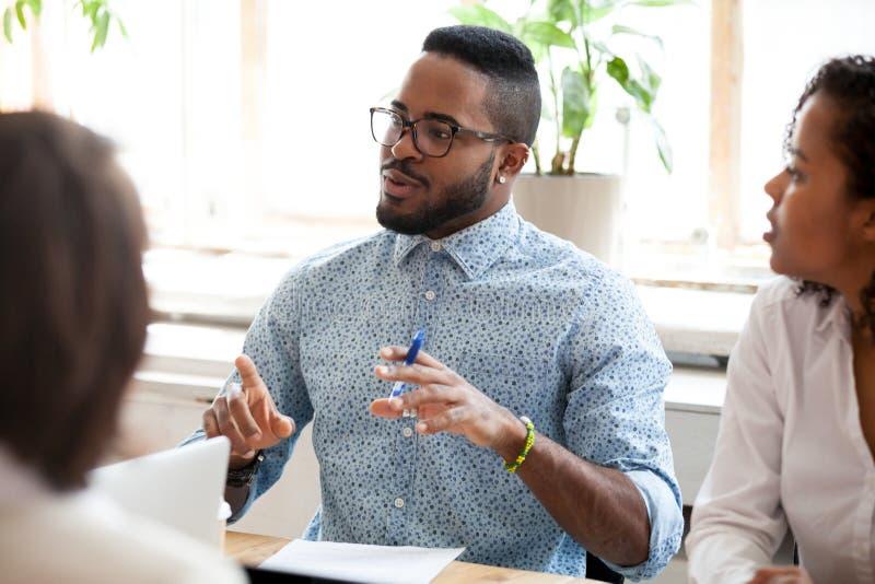 Afrikaanse Amerikaanse zakenman die over ideeën bij briefing spreken stock foto's