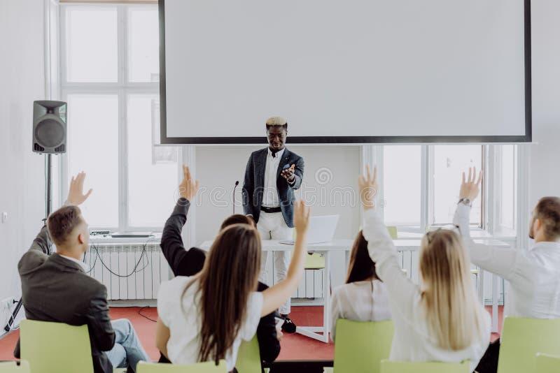 Afrikaanse Amerikaanse zakenman die presentatie geven die project bespreken met multi-etnische groep bij collectieve opleiding He royalty-vrije stock afbeelding