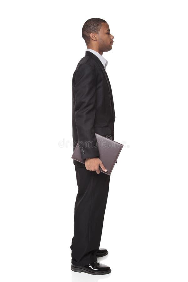 Afrikaanse Amerikaanse zakenman het dragen blocnote stock afbeelding