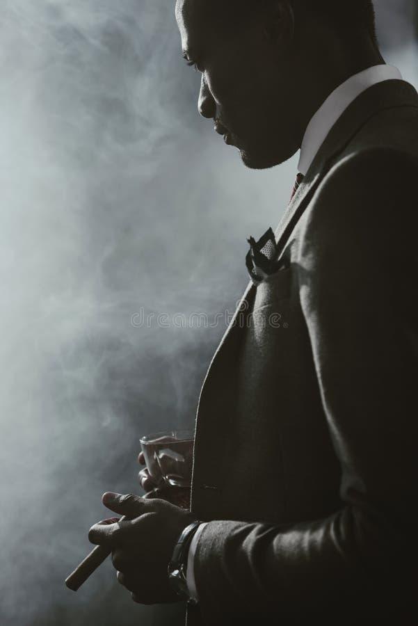 Afrikaanse Amerikaanse zakenman in kostuum met glas van whisky rokende sigaar royalty-vrije stock foto