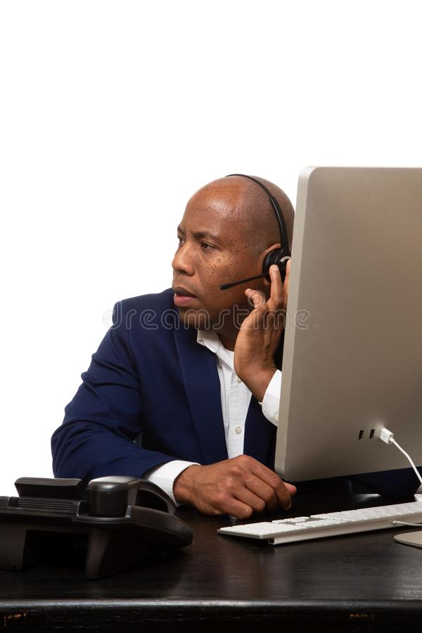 Afrikaanse Amerikaanse Zakenman Listens Through Headset bij Bureau stock afbeelding