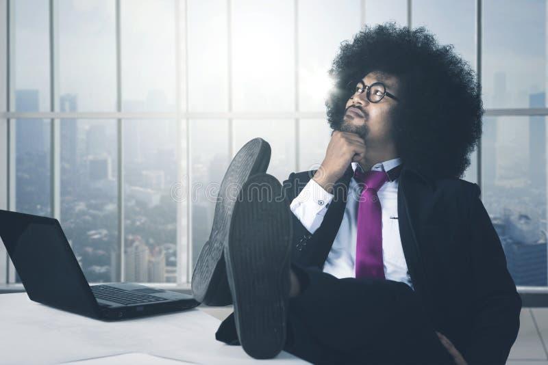Afrikaanse Amerikaanse zakenman met voeten op bureau het denken royalty-vrije stock foto