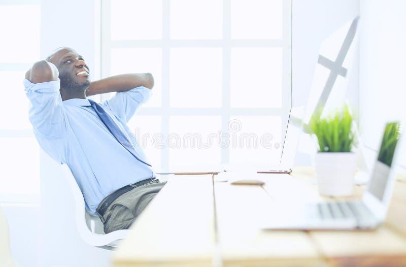 Afrikaanse Amerikaanse zakenman op hoofdtelefoon die aan zijn laptop werken royalty-vrije stock fotografie