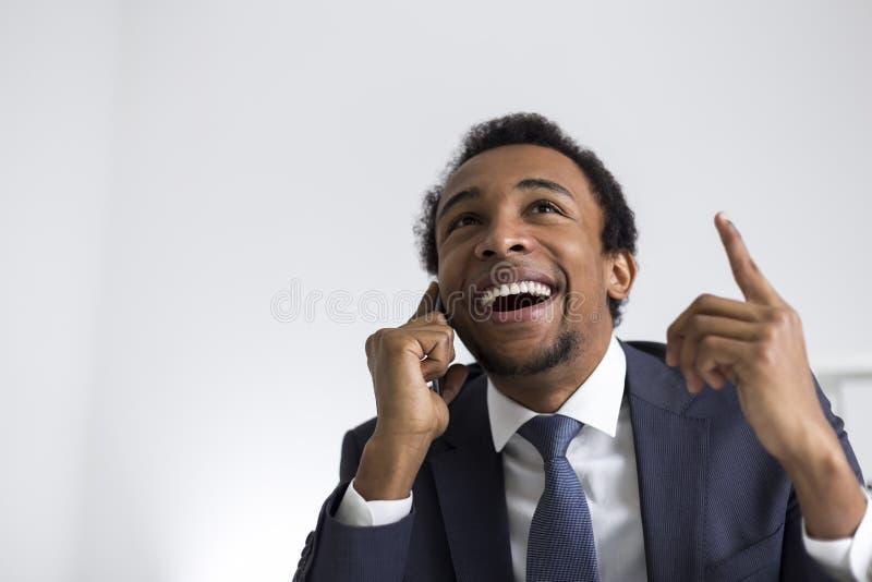 Afrikaanse Amerikaanse zakenman op telefoon in bureau royalty-vrije stock foto's