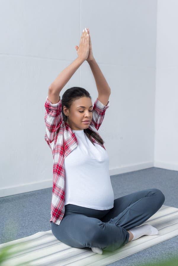 Afrikaanse Amerikaanse zwangere vrouw die met gesloten ogen en namaste mudra op yoga mediteren stock afbeeldingen