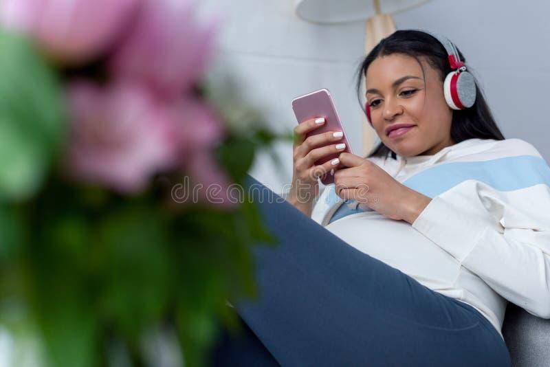Afrikaanse Amerikaanse zwangere vrouw het luisteren muziek met hoofdtelefoons stock afbeelding