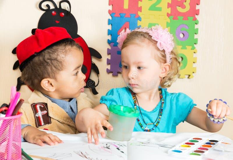 Afrikaanse Amerikaanse zwarte jongen en meisjestekening met kleurrijke potloden in kleuterschool in kleuterschool stock foto