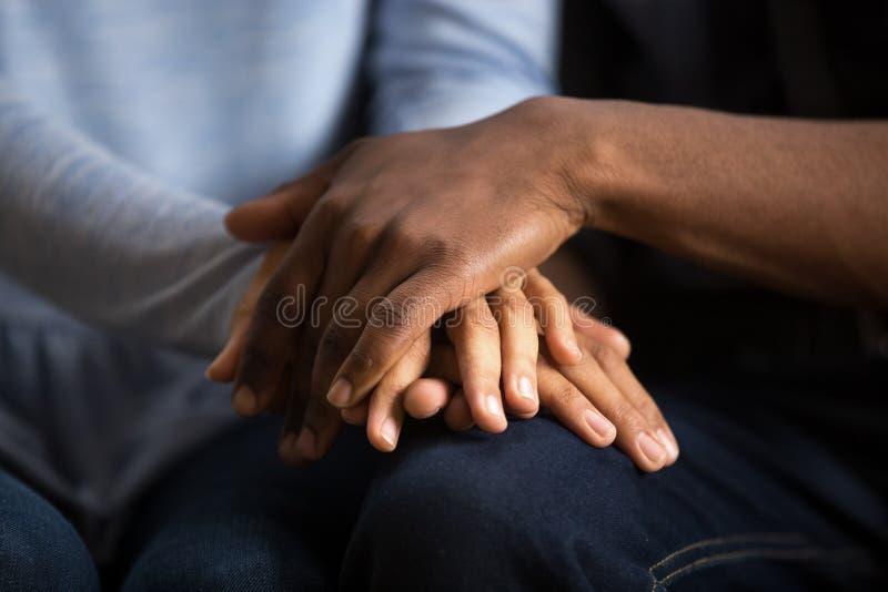 Afrikaanse Amerikaanse zwarte van de paarechtgenoot en vrouw holdingshanden, cl stock foto's
