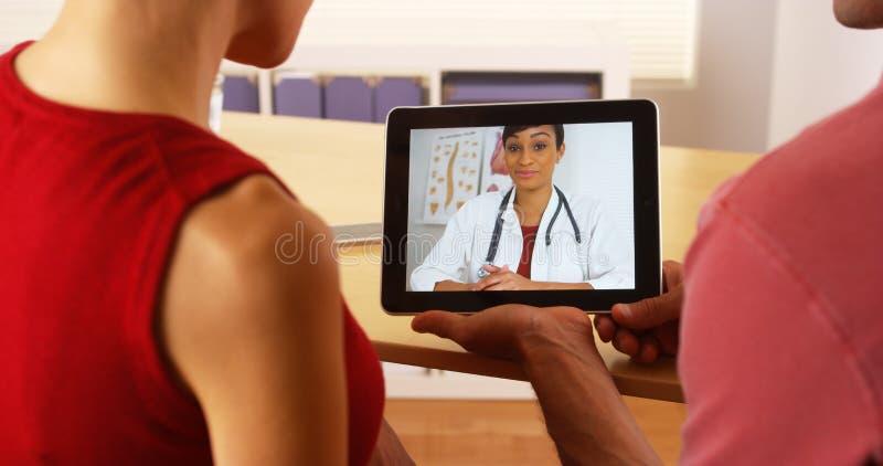 Afrikaanse arts die op tablet spreken stock foto
