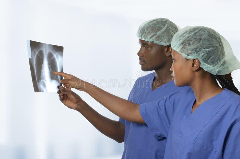 Afrikaanse artsen die op x-ray beeld van longen letten royalty-vrije stock foto