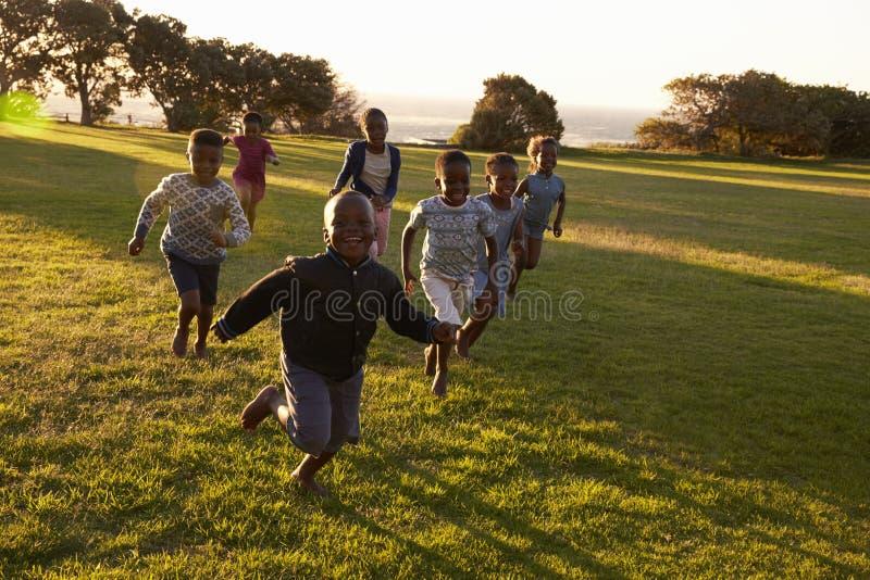 Afrikaanse basisschooljonge geitjes die aan camera op een gebied lopen royalty-vrije stock afbeelding