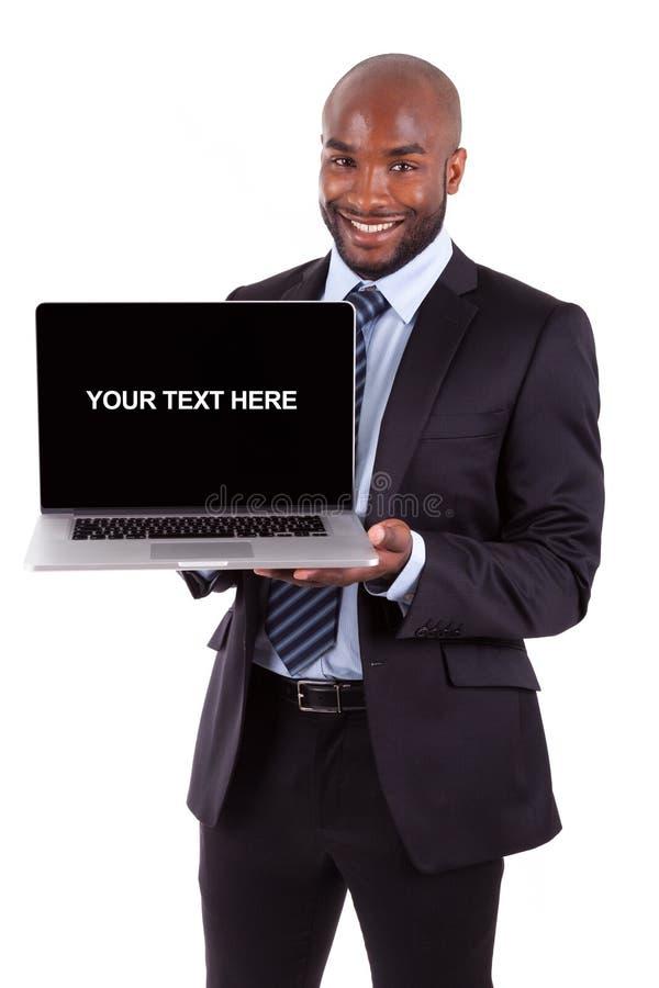 Afrikaanse bedrijfsmens die het laptop scherm toont stock afbeelding