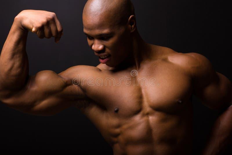 Afrikaanse bodybuilder op zwarte stock fotografie