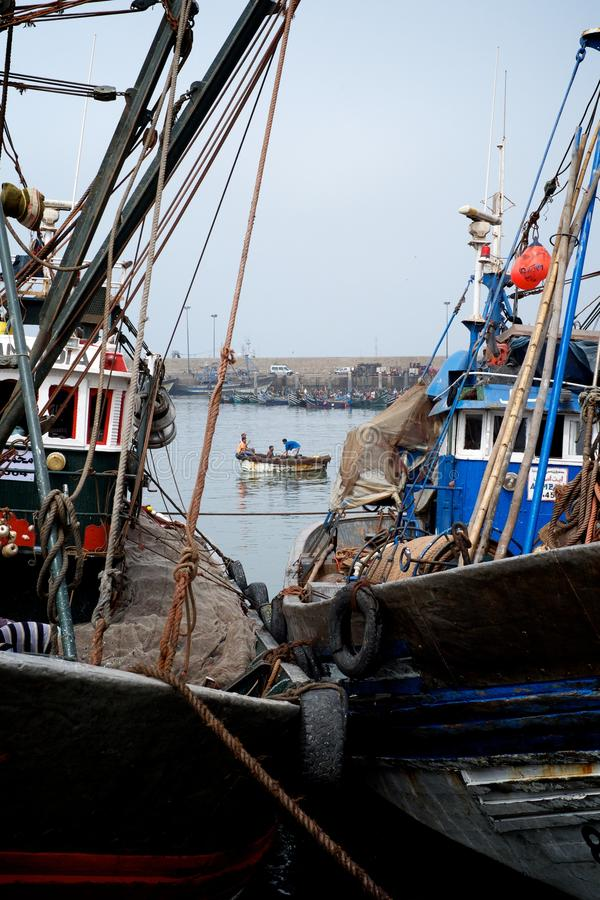 Afrikaanse die vissersboten in een haven naast de groothandelsmarkt worden gedokt stock foto's