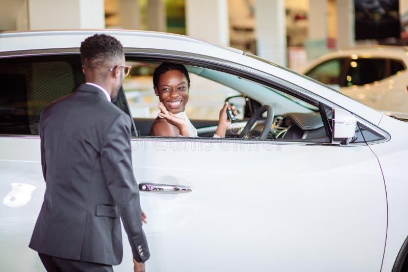 Afrikaanse die vrouw door nieuwe auto, gift voor mijn mooie vrouw wordt verrast royalty-vrije stock afbeelding