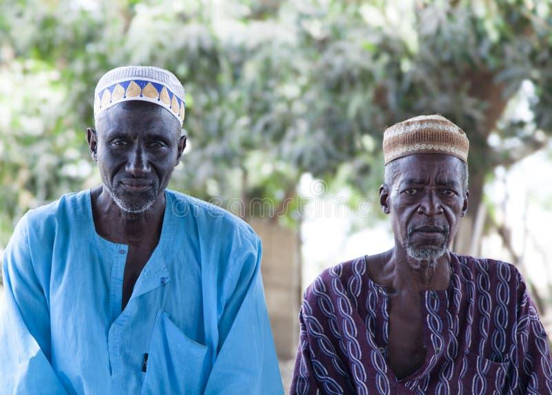 Afrikaanse dorpsoudsten in traditionele kleurrijke kleren en moslimkappen royalty-vrije stock foto