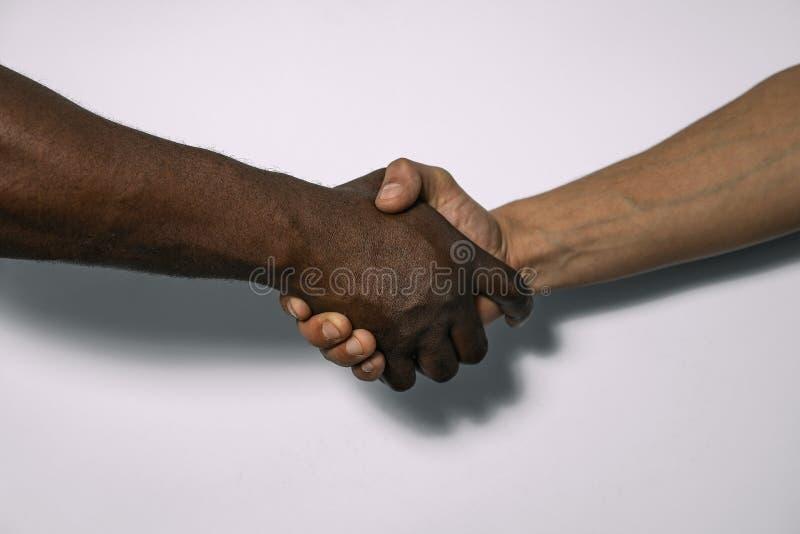 Afrikaanse en Europese handdruk als teken van vriendschap, groet, overeenkomst of overeenkomst stock foto's
