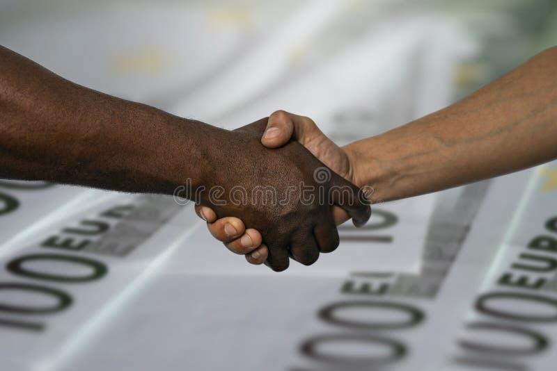 Afrikaanse en Europese handdruk als teken van vriendschap, groet, overeenkomst of overeenkomst, tegen de achtergrond van 100 euro royalty-vrije stock foto's