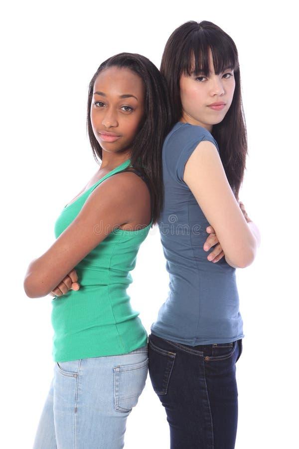 Afrikaanse en Japanse meisjes ernstige gemiddelde chagrijnige blikken stock fotografie