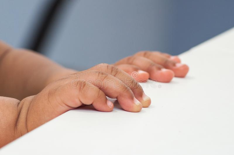 Afrikaanse handen van baby het stellen op witte lijst royalty-vrije stock afbeelding