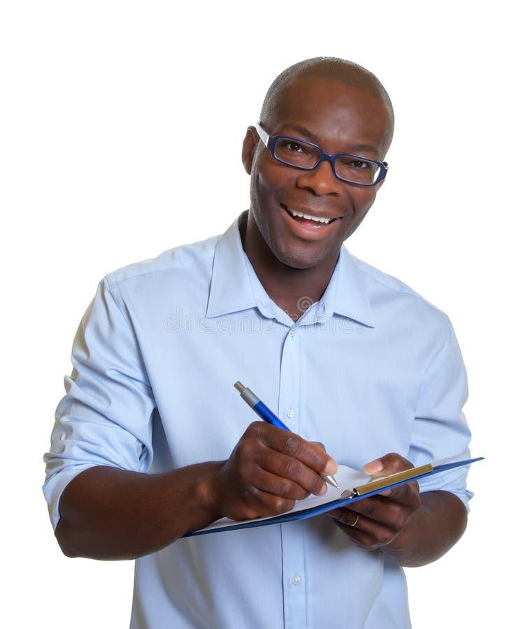 Afrikaanse het bedrijfsmens schrijven nota's over een klembord royalty-vrije stock foto's