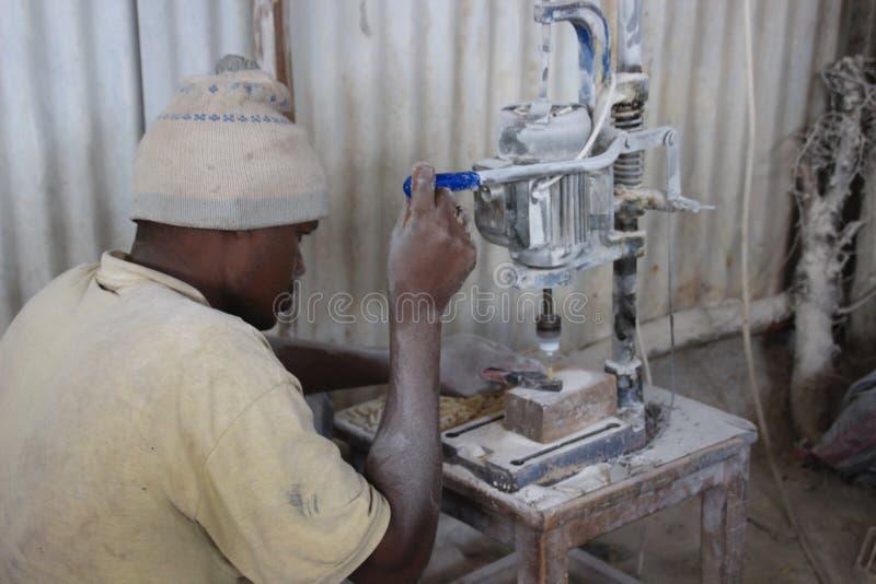 Afrikaanse jonge mannelijke arbeider bij een herinneringsfabriek die met een machine werken royalty-vrije stock foto's