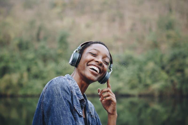 Afrikaanse jonge vrouw die aan muziek in aard luisteren royalty-vrije stock foto's