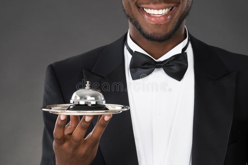 Afrikaanse Kelner Holding Service Bell royalty-vrije stock afbeeldingen