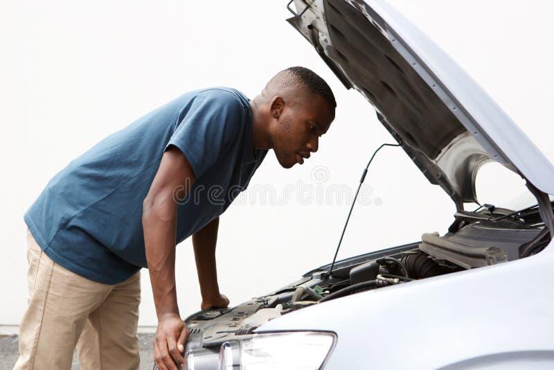 Afrikaanse kerel die onder de kap van zijn opgesplitste auto kijken stock foto