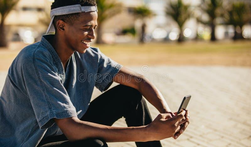 Afrikaanse kerel die telefoon in openlucht met behulp van royalty-vrije stock afbeelding