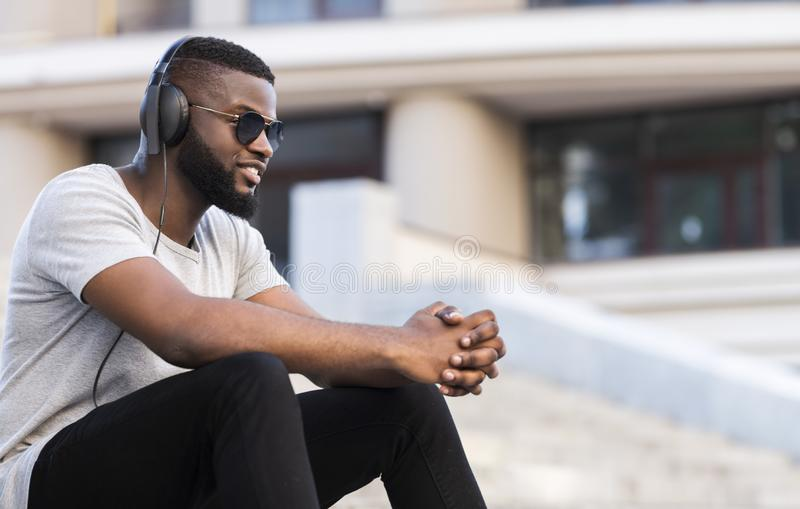 Afrikaanse kerel in hoofdtelefoons die aan muziek luisteren die goede stemming hebben royalty-vrije stock foto's