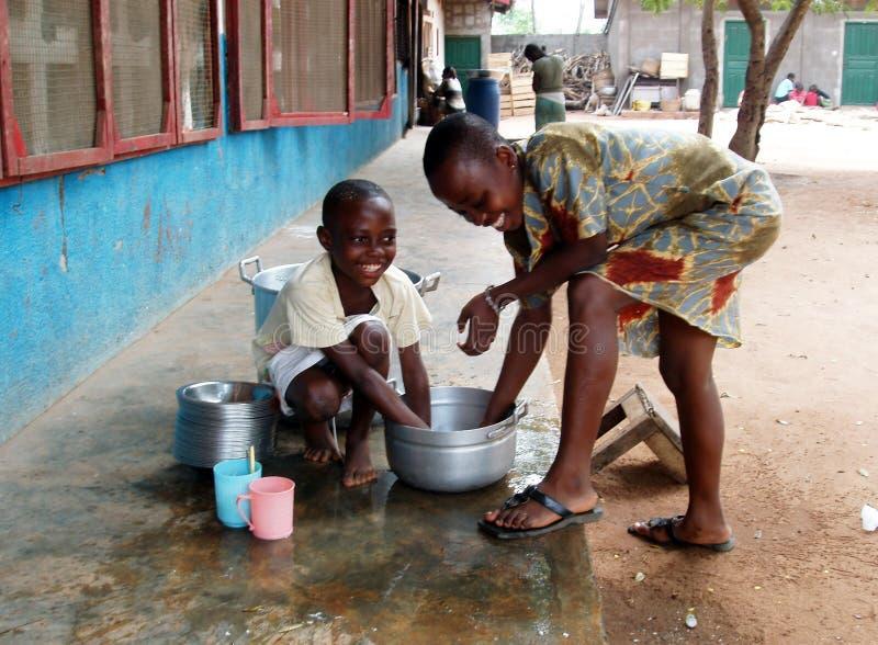Afrikaanse kinderen die potten wassen royalty-vrije stock afbeeldingen