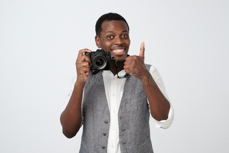 Afrikaanse knappe de foto van de mensenholding camera en glimlachen, die duim tonen stock foto