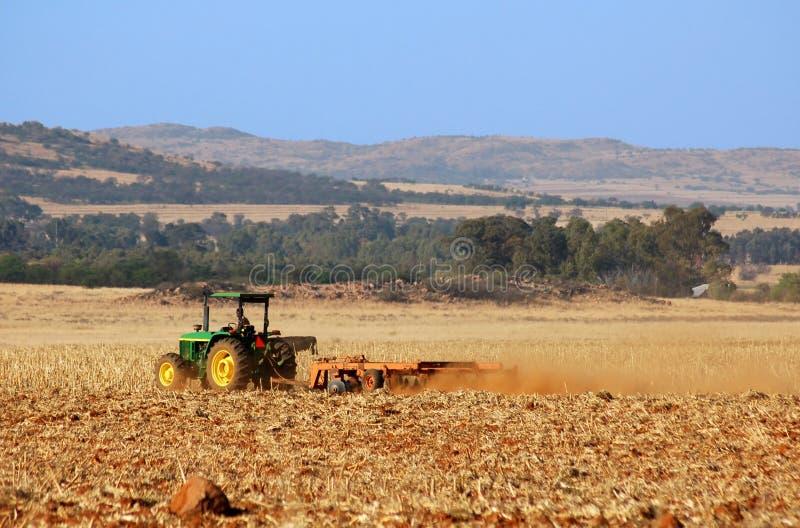 Afrikaanse landbouwer die zijn gebied werkt stock foto's