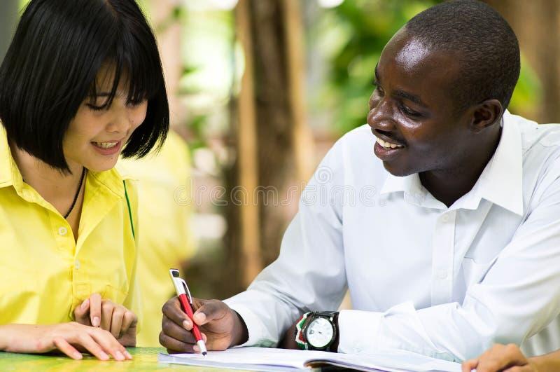 Afrikaanse leraar die Aziatische student over vreemde talen onderwijzen stock afbeelding