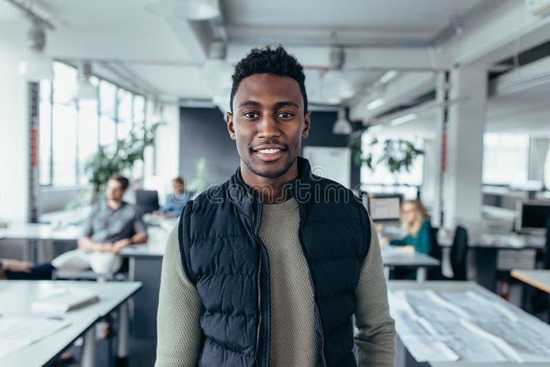 Afrikaanse mannelijke ontwerper die zich in modern bureau bevinden stock afbeeldingen
