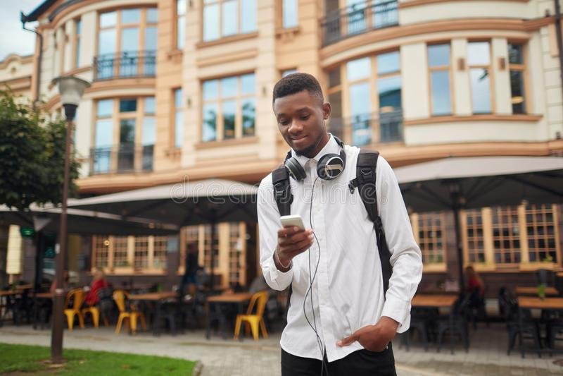 Afrikaanse mens die en elektronische kaart in slimme telefoon lopen bekijken royalty-vrije stock afbeeldingen