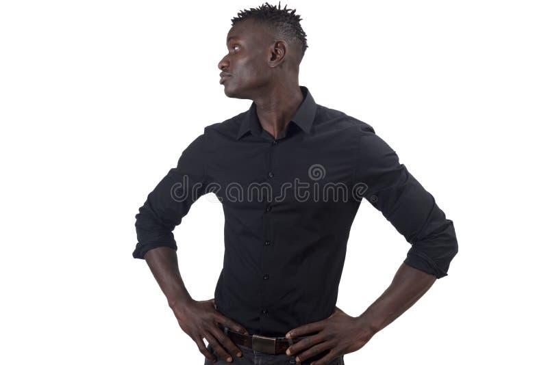Afrikaanse mens die met wapens op taille aan de ernstige kant kijken, royalty-vrije stock fotografie